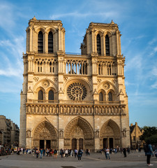 View of Notre-Dame Cathedral in sunset sunrays. Unidentified people present on picture.