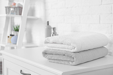 Stack of fresh towels on cabinet in bathroom. Space for text