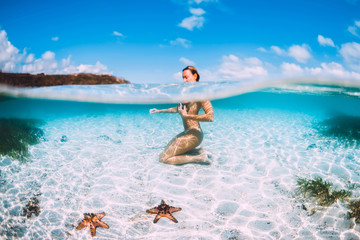 Naked woman swim in blue ocean with starfish, underwater in tropical sea