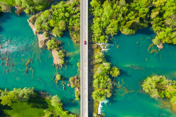 Red car crossing road bridge over Mreznica river in Croatia, overhead shot of countryside landscape, waterfalls and trees in spring
