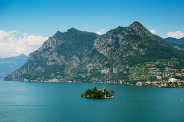 Loreto island in the middle of the Iseo lake with montains in the background