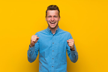 Blonde man over isolated yellow wall celebrating a victory in winner position