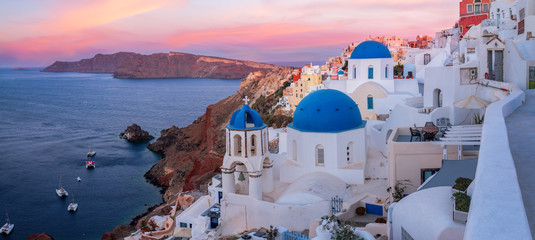 The famous three blue domes in Santorini at sunset