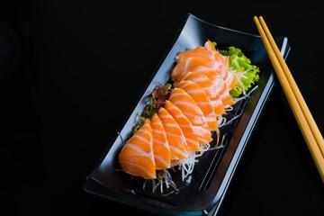 Łososiowy Sashimi na Czarnym Ceramicznym talerzu, czarny tło.