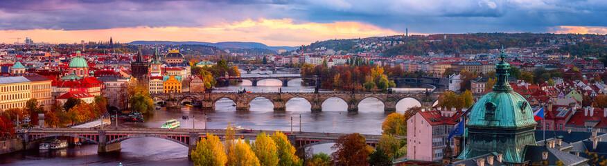 Zachód słońca w praskiej panoramie, widok na historyczne mosty, stare miasto i Wełtawę z popularnego punktu widokowego w parku Letna, jesienny krajobraz w świetle zachodzącego słońca z niesamowitym pochmurnym niebem, Republika Czeska