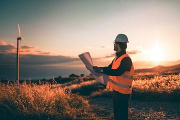 Giovane Ingegnere Aerospaziale con caschetto bianco e gilet arancione, sta controllando il progetto sul foglio di una turbina di un impianto eolico in montagna. Concetto ingegneria ed energia pulita