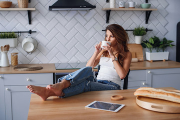 Cheerful girl in white t-shirt using tablet computer while relaxing in a chair at home in cozy kitchen.
