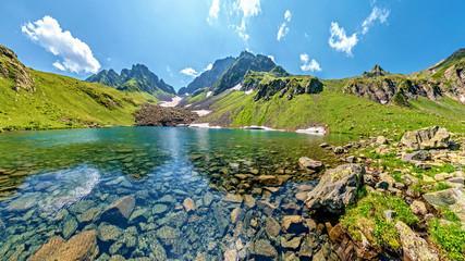 Turquoise water in lake Kalalish with peaks in background, Svaneti mountains, Georgia, Asia