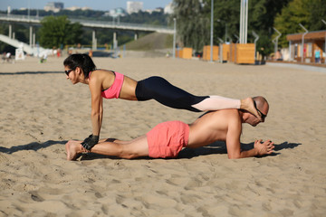 Pretty woman and handsome muscular man doing double plank with girl atop