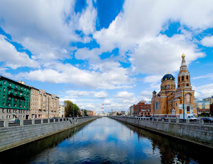 Amazing spring panorama of the city from bridge. Beautiful clouds and are reflected in the river. There is  a beautiful Orthodox church on the right.