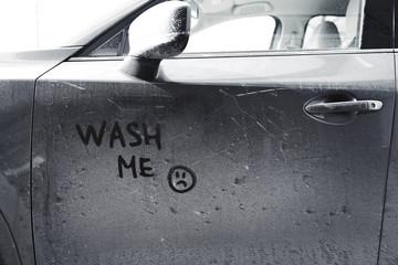 Inscription WASH ME and sad smiley on car door, closeup