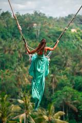 Opalona młoda kobieta jedzie na długiej huśtawce w długiej turkusowej sukni. Wyspa bali. Las tropikalny w tle. Podróż i radość