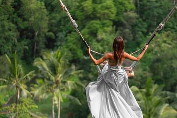 Woman in long white dress swinging in the jungle, Bali