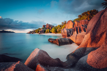 Unique shaped granite boulders and a dramatic sunset at Anse Source d'Argent beach, La Digue island, Seychelles. Long Exposure
