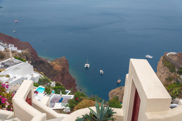 Houses and terraces of the village of Oia above a bay with red cliffs