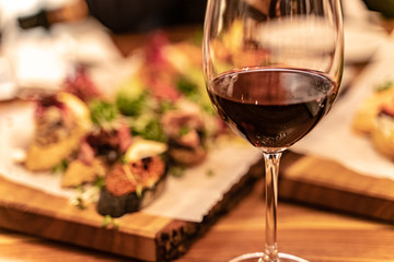 Red wine glasses on a wooden plank with defocused antipasto catering platter at the background