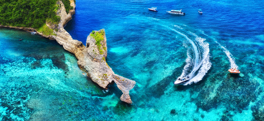 Fast boat at the sea in Bali, Indonesia. Aerial view of luxury floating boat on transparent turquoise water at sunny day. Panoramic seascape from air. Top view from drone. Travel - image