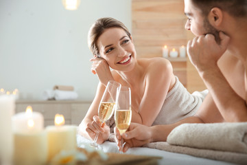 Romantic young couple with champagne in spa salon