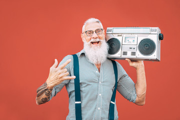 Happy senior man listening to music with boombox outdoor - Crazy hipster male having fun dancing with vintage stereo - Concept of elderly people lifestyle