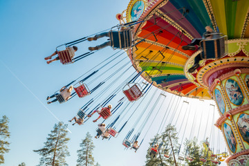 Kouvola, Finland - 18 May 2019: Ride Swing Carousel in motion in amusement park Tykkimaki and aircraft trail in sky.