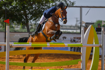 Young rider jumping over the obstacles during the horse jumping competition