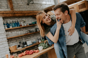 Lovely couple having fun together at rustic kitchen