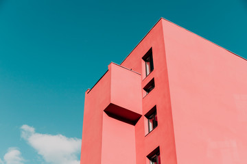 Widok z dołu na różowy, nowoczesny dom i niebo. Vintage pastelowe kolory, minimalistyczna koncepcja.