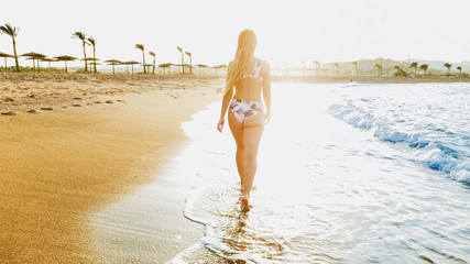 Rear view image of beautiful sexy barefoot woman in bikini walking in calm sea waves on the beach towards the sunset