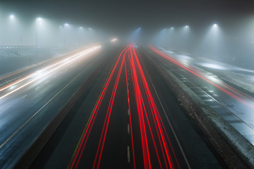 Car trails on a wet and foggy highway at night.