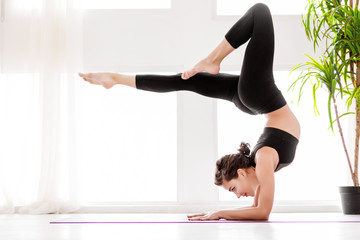 Young healthy fitness beautiful woman female doing vrischikasana yoga posture and yoga workout on yoga mat at yoga studio in morning. Healthy lifestyle, morning workout concept