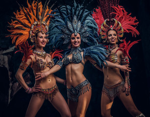 Three beautiful smiling womans in traditional brasilian carnaval costumes are posing for photographer at studio.