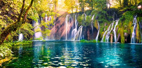 Ostatnie słońce oświetla wodospad z czystą wodą w Parku Narodowym Plitvice. Kolorowa wiosny panorama zielony las z błękitnym jeziorem. Wspaniały widok na okolicę z Chorwacji, Europy.
