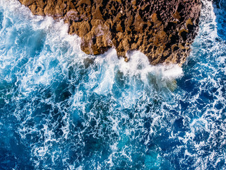 Top view Azure blue sea with waves beating on beach and rocks. Aerial photo.