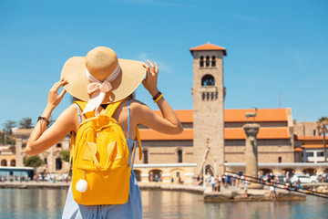 Asian girl traveler with big hat and backpack on vacation in the popular Greek island of Rhodes