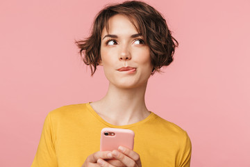 Thinking dreaming young beautiful woman posing isolated over pink wall background using mobile phone.