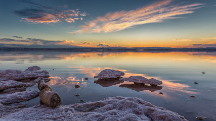 A tree trunk lies in the salt lake. The lagoon of Torrevieja in Spain after sunset with beautiful reflections in the water. The salt forms interesting shapes, like a mushroom.
