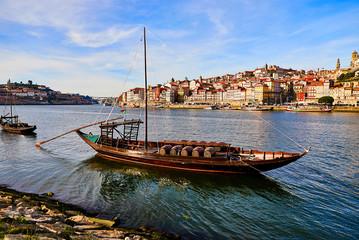 """Typowe portugalskie drewniane łodzie, zwane """"barcos rabelos"""", przewożące beczki z winem na rzece Douro z widokiem na Villa Nova de Gaia w Porto, Portugalia"""