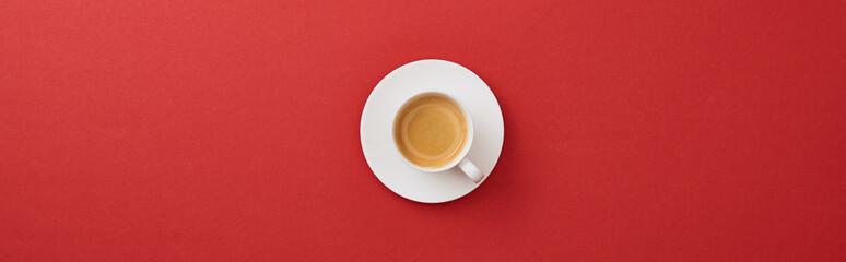 widok z góry biały kubek ze świeżą kawą na talerzyk na czerwonym tle, panoramiczny strzał
