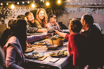 Happy family cheering with red wine at barbecue dinner outdoor - Different age of people having fun at weekend meal - Food, taste and summer concept - Focus on hands toasting