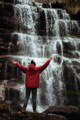 Girl in red jacket by the waterfall