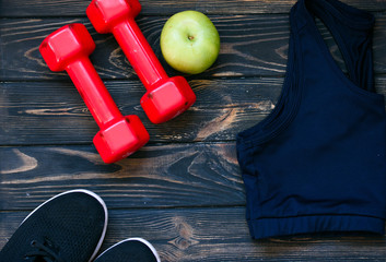 sports top, red dumbbells, green apple, sports shoes