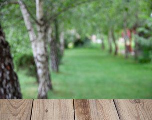 Blurred background of forest park garden with wooden table