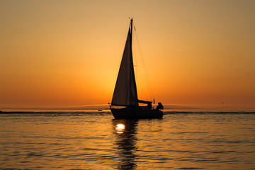 yacht with a sail at sunset in the sea