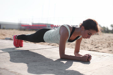 Close up of young pretty caucasian muscular woman doing plank exercise outndoor at the ground. Concept of health and sport lifestyle. Athletic Body of european girl...
