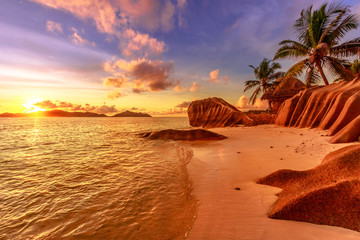 Seychelles, La Digue, Anse Source d'Argent at sunset. Landscape with sky and colorful clouds on rock stone of granite with palm trees. Sun at twilight on the calm sea on the horizon.