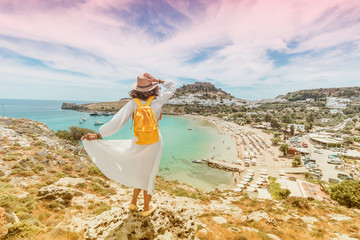 Happy asian woman travels in Greece. Having fun at the stunning view on sea resort and old town of Lindos on the mountain