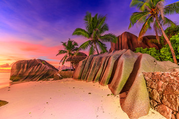 Dramatic colorful sky dusk at scenic Anse Source d'Argent in Seychelles, La Digue. Landscape with shaped rock stone of granite and palm trees. Source d'Argent Beach paradise of Seychelles.