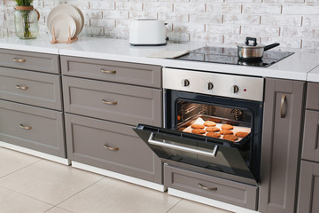 Open oven with tasty homemade cookies in kitchen