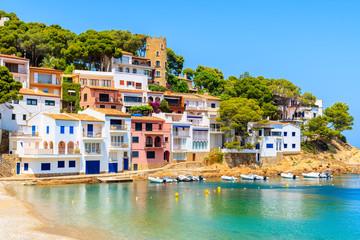 View of colorful houses in sea bay with beach in Sa Tuna coastal village, Costa Brava, Spain