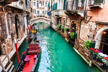 Scenic canal with gondolas and old architecture in Venice, Italy. famous travel destination